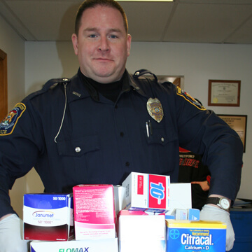 Officer Taking Back Prescription and Non-prescription Drugs during Takeback event hosted by MAMDP